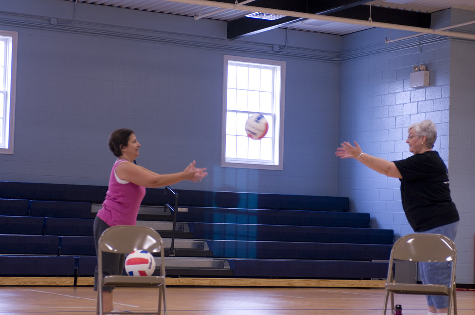 The two older women pictured here on the wooden floor of an indoor basketball court, were participating in an exercise class consisting of s
