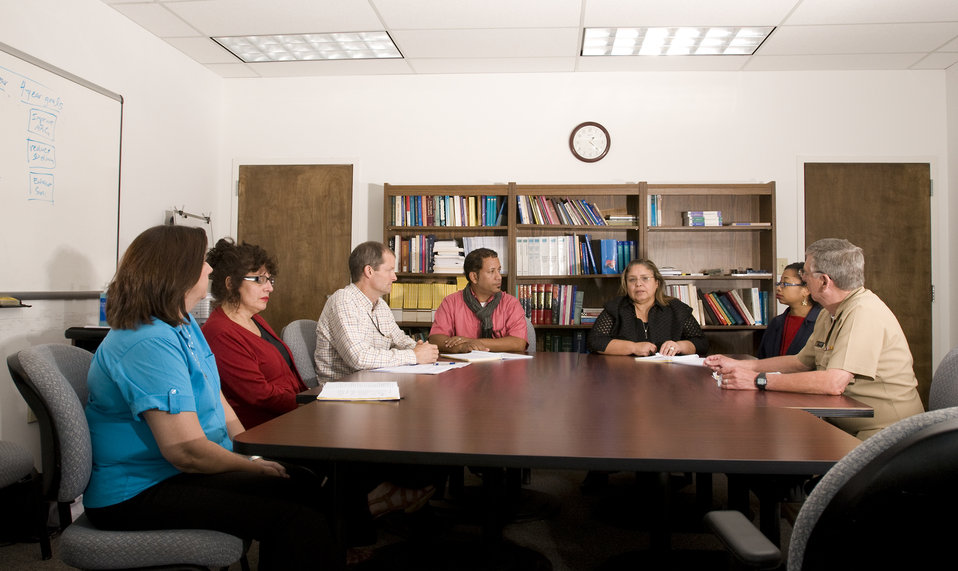 This image depicts a group of healthcare workers seated at a table discussing a strategy they would be implementing, which would guide them