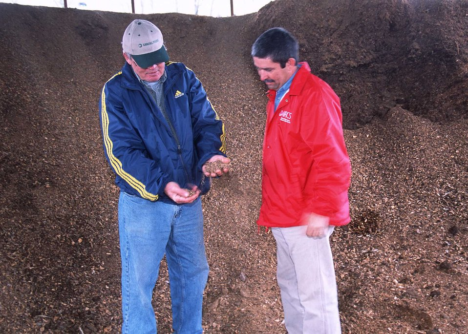 discussing composting from turkey manure and woodchips with cooperator in Benton, Arkansas.