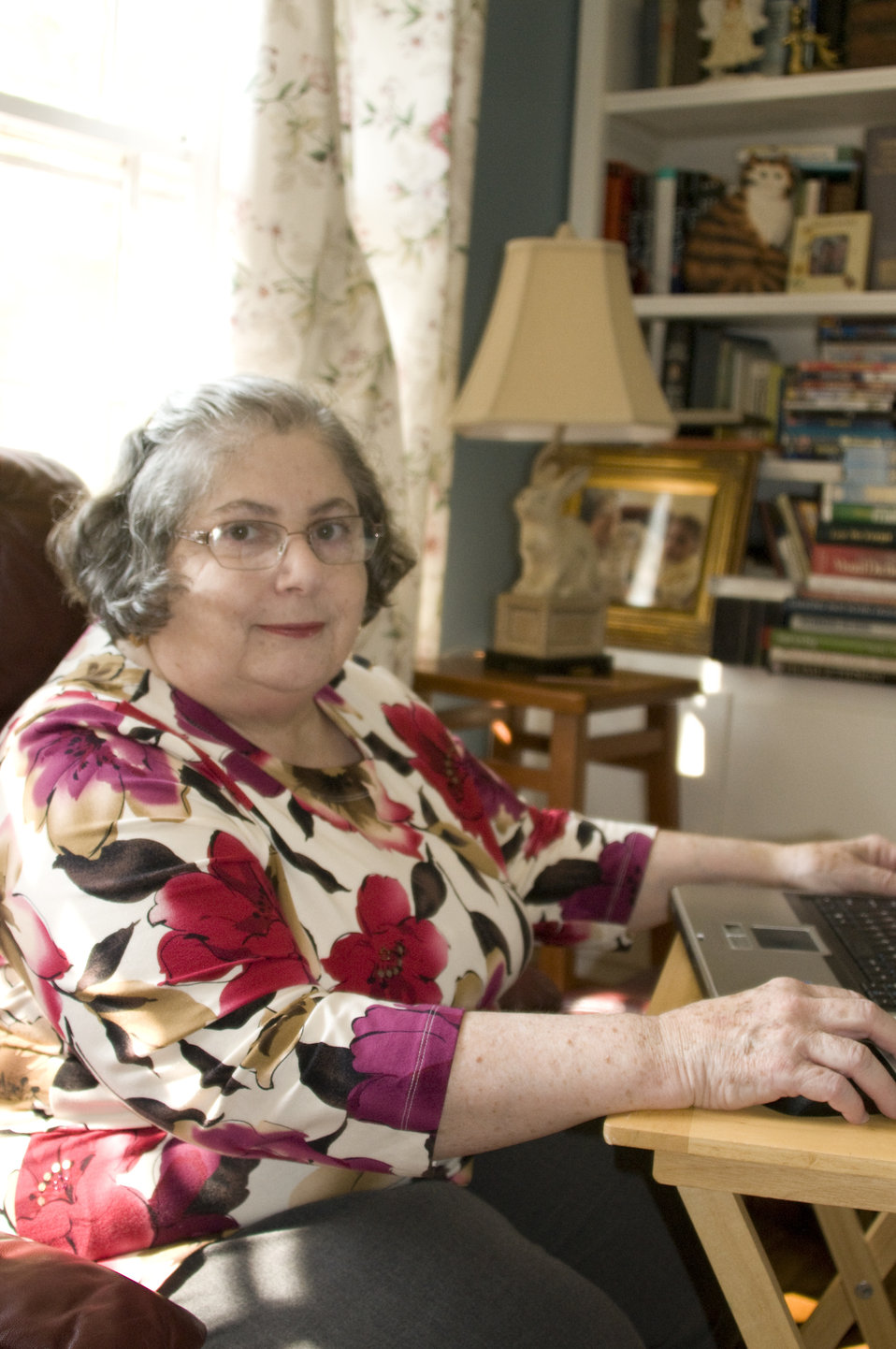 Seated at a small folding table, atop which was a laptop computer, this female rheumatoid arthritis patient was shown logging on to her work