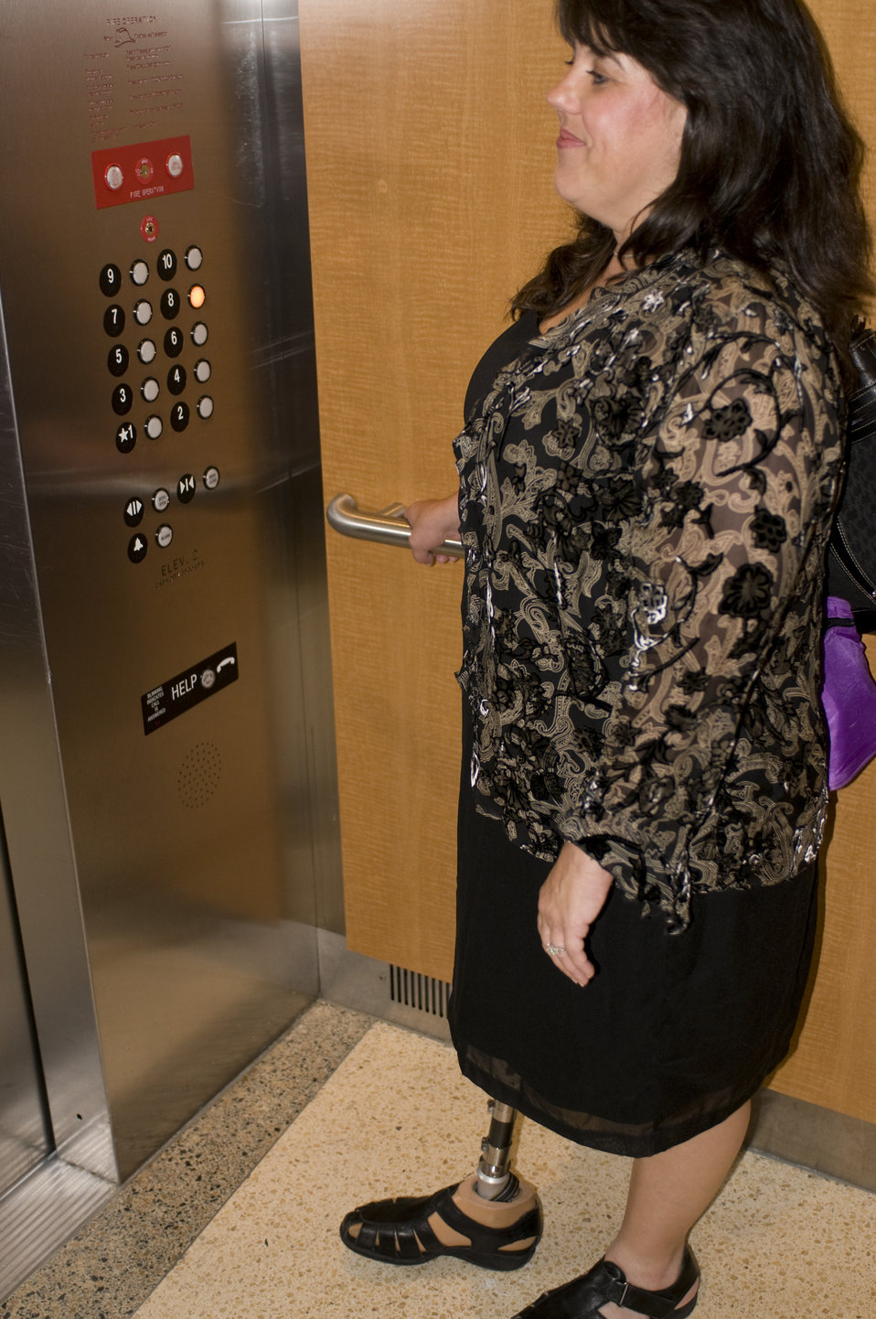 After having boarded this elevator, the woman pictured in this photograph had pressed the desired button, choosing the eighth floor as her d