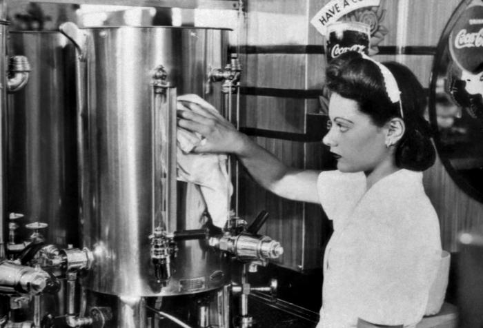 This historic 1950s photograph depicted a worker cleaning a stainless steel beverage dispenser that was located in the food preparation area