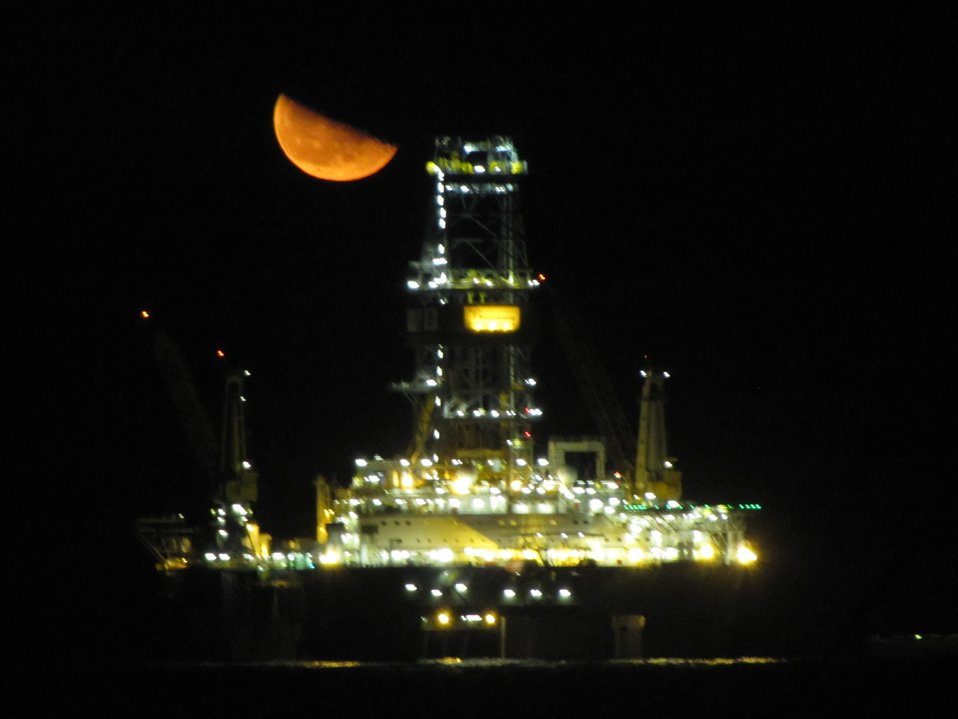 A view of a Deepwater Horizon disaster relief drill vessel with a half moon rising? setting?