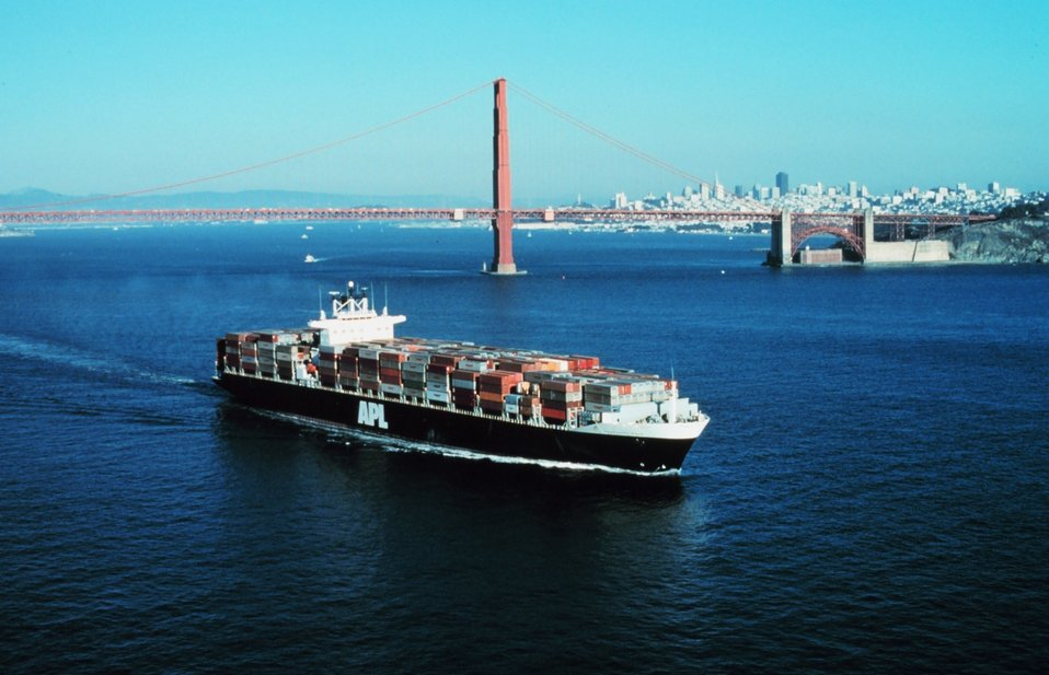 An outward bound containership with the Golden Gate and San Francisco skyline in the background.