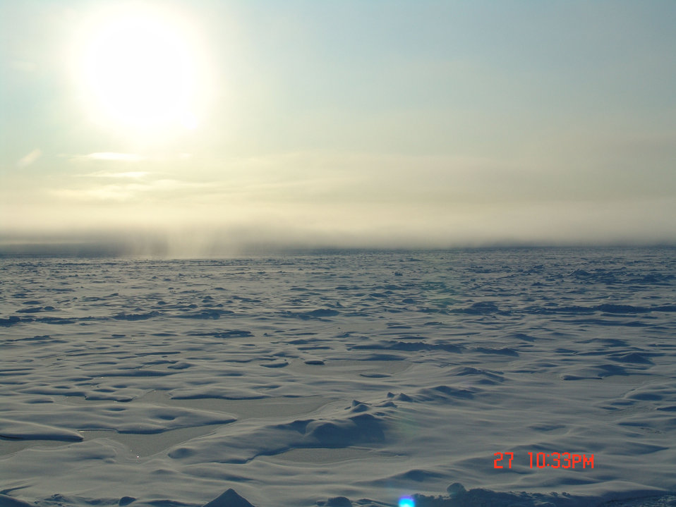 Hummocky multi-year ice with ridges and refrozen melt ponds.  Frozen fog in the distance with either a show shower or possible illumination of ice crystals below sun.