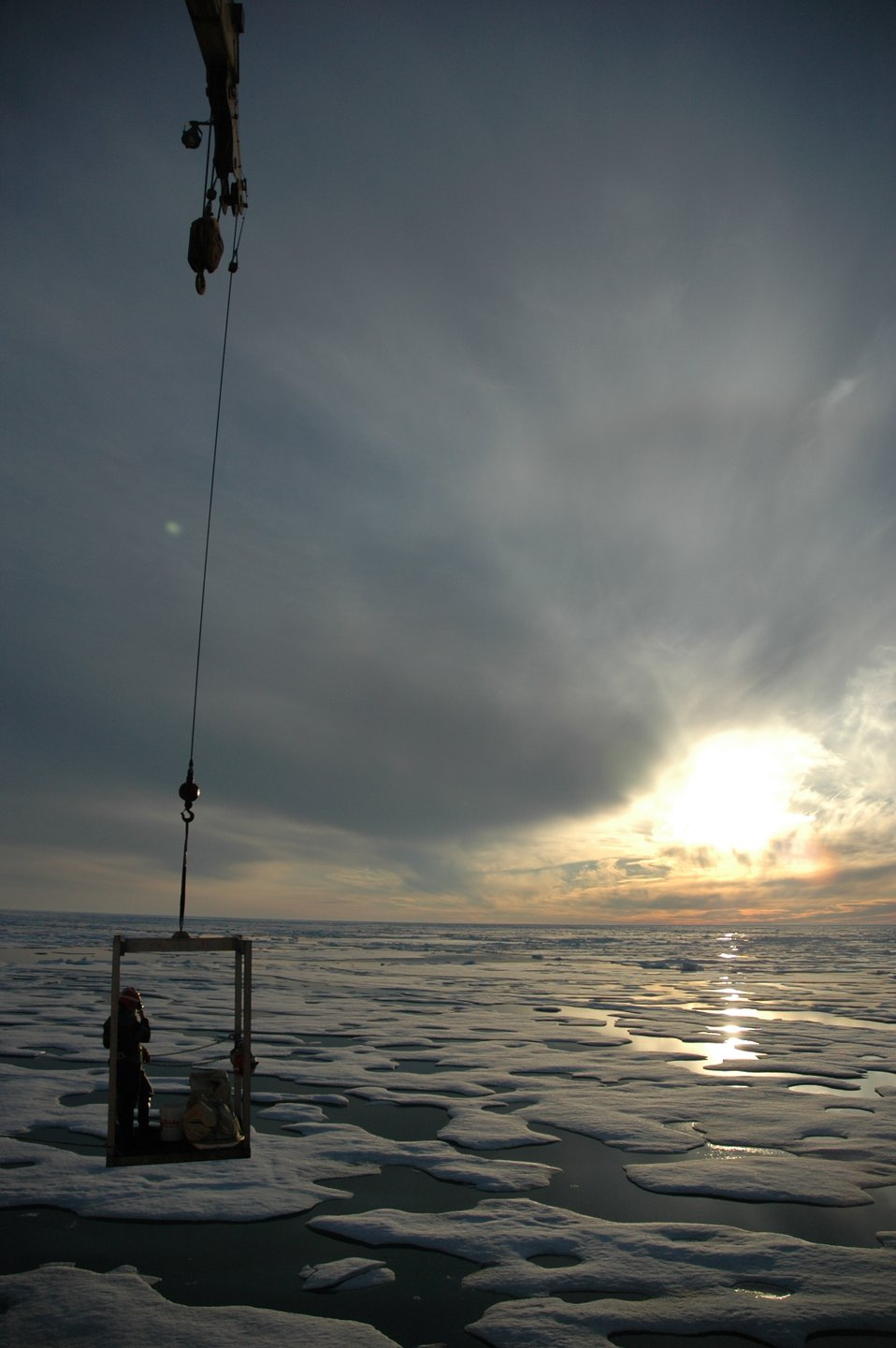 Transportation off the ship as a scientist is being transported to the ice surface from the USCG Icebreaker HEALY under the midnight sun.