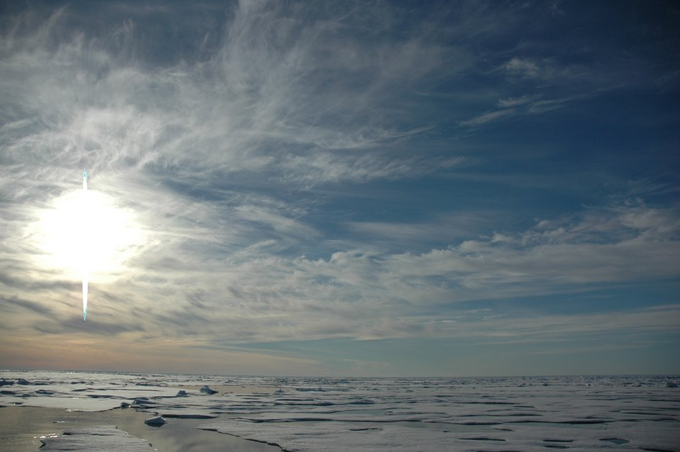 Midnight sun, melting Arctic ice, open leads, and cirrus clouds.