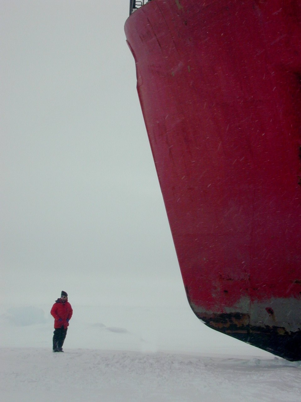 Scientist standing next to the bow of the U.S. Coast Guard Icebreaker HEALY.
