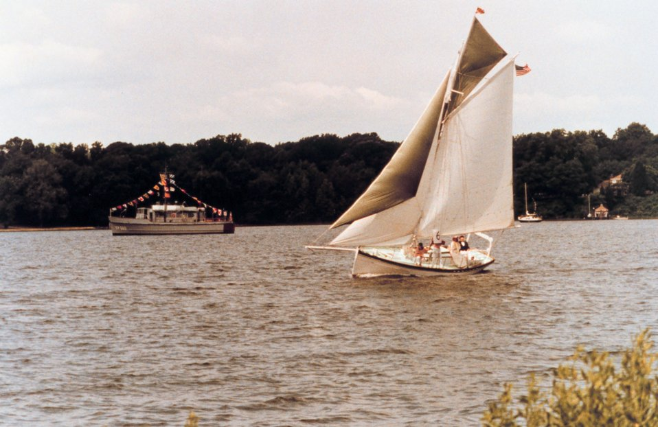 A Navy YP dressed for a holiday while the GALATEA, an old gaff-rigged cutter, travels the waters of the St. Mary's River