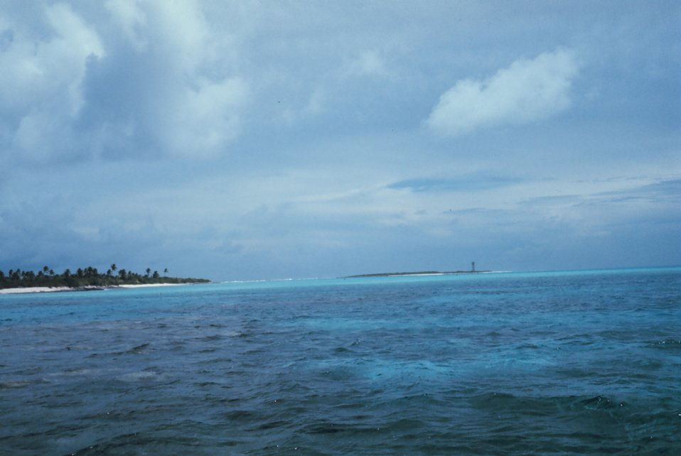 A low lying atoll with a navigation aid on a smaller outlying island.