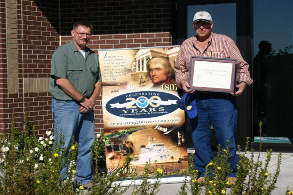 Cooperative Weather Observer Mr. Joe Alexander of Burris, Wyoming (right) recently received the prestigious John Campanius Holm Award on behalf of his family from Data Acquisition Program Manager Ralph Estell of NOAA's National Weather Service in Rivert
