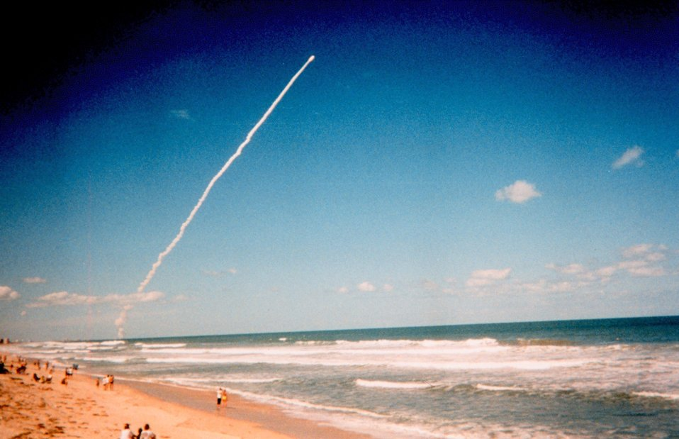 A space shuttle launch from Cape Canaveral provides a dramatic site for beach-goers.
