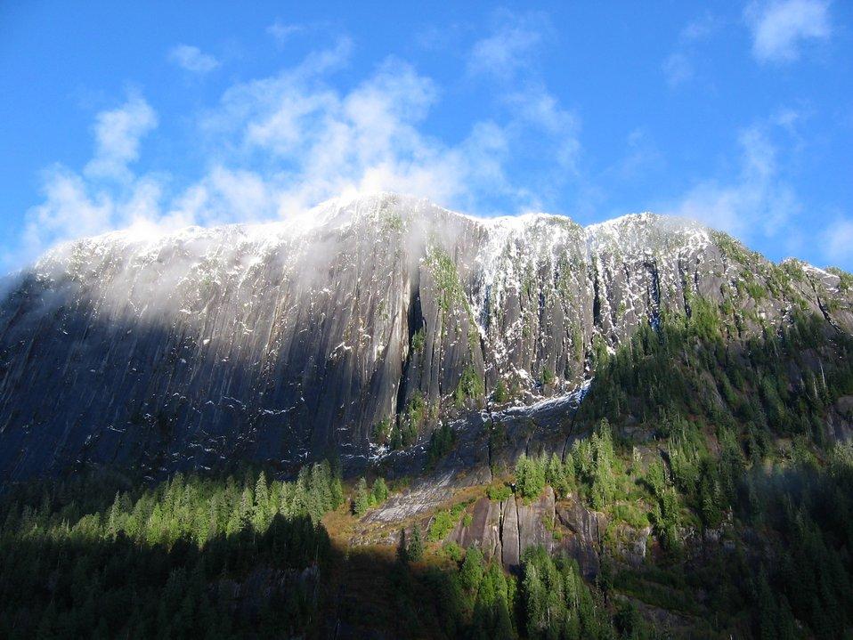 Sprinkles of snow dot precipitous cliffs.