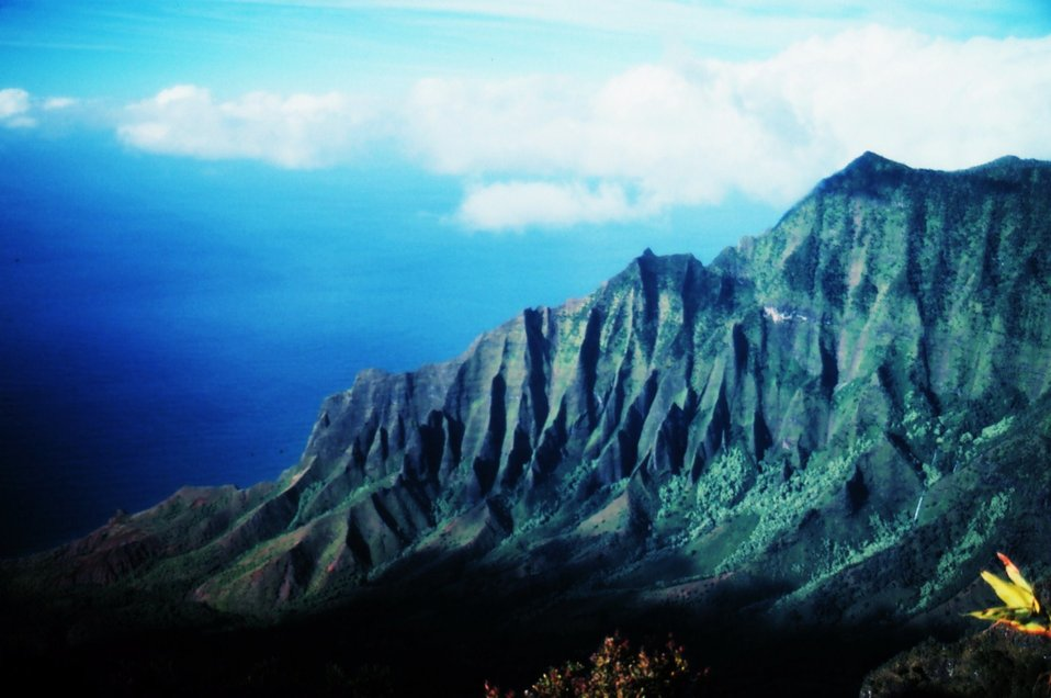 A knife-edge ridge on Kauai on the Na Pali coast.  The ridge looms over the Kalalau Valley which is veiled in shadows in the lower fourth of the picture.