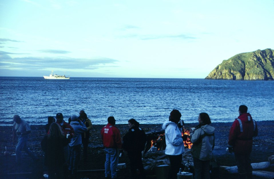 NOAA Ship RAINIER crew beach party at Chowiet Island in the Semidi Island group southwest of Kodiak Island.  RAINIER in background.