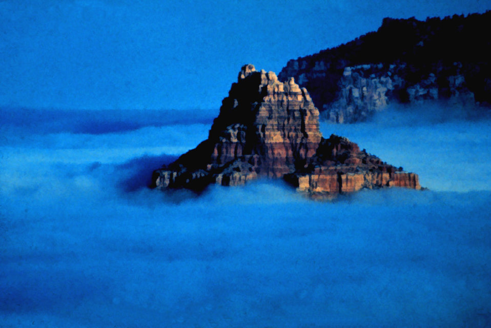 A rocky peak rises from a sea of fog in an Arizona valley