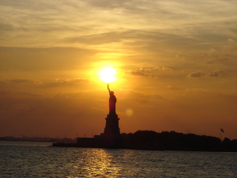The Statue of Liberty at sunset holding the torch of freedom aloft.
