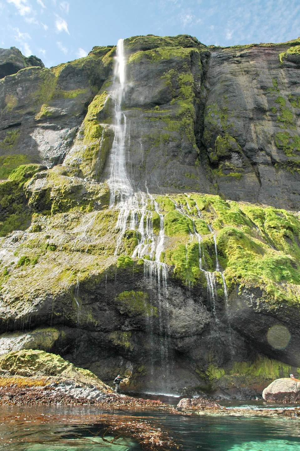 A beautiful waterfall flowing over moss-covered rocks to a kelp forest