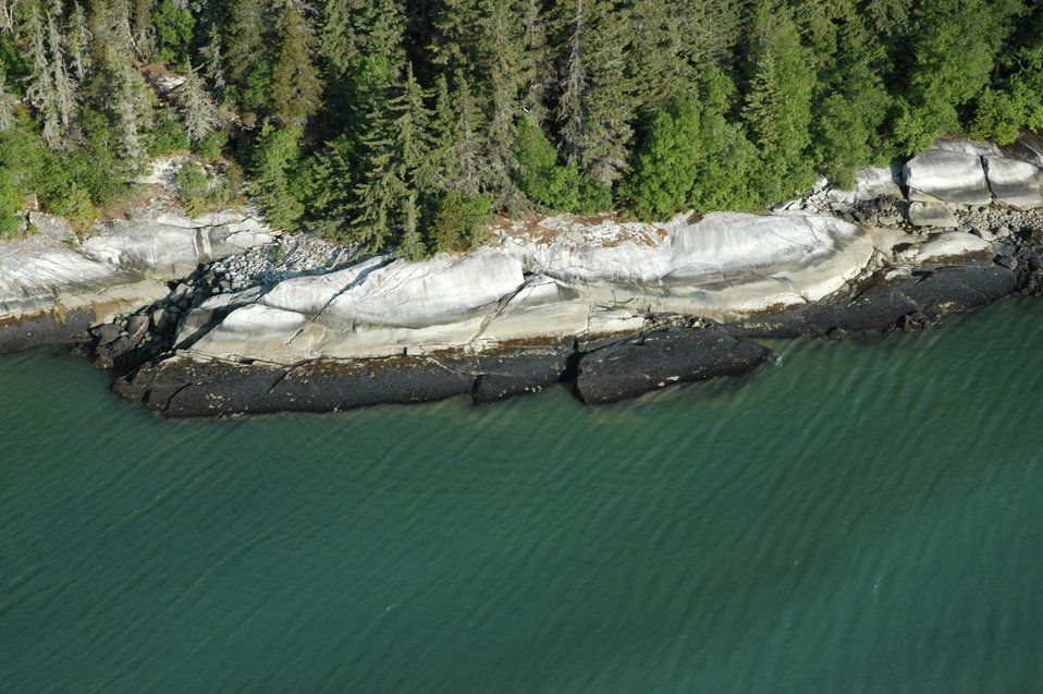 Aerial photograph. Tidal banding on a smooth rock shoreline.