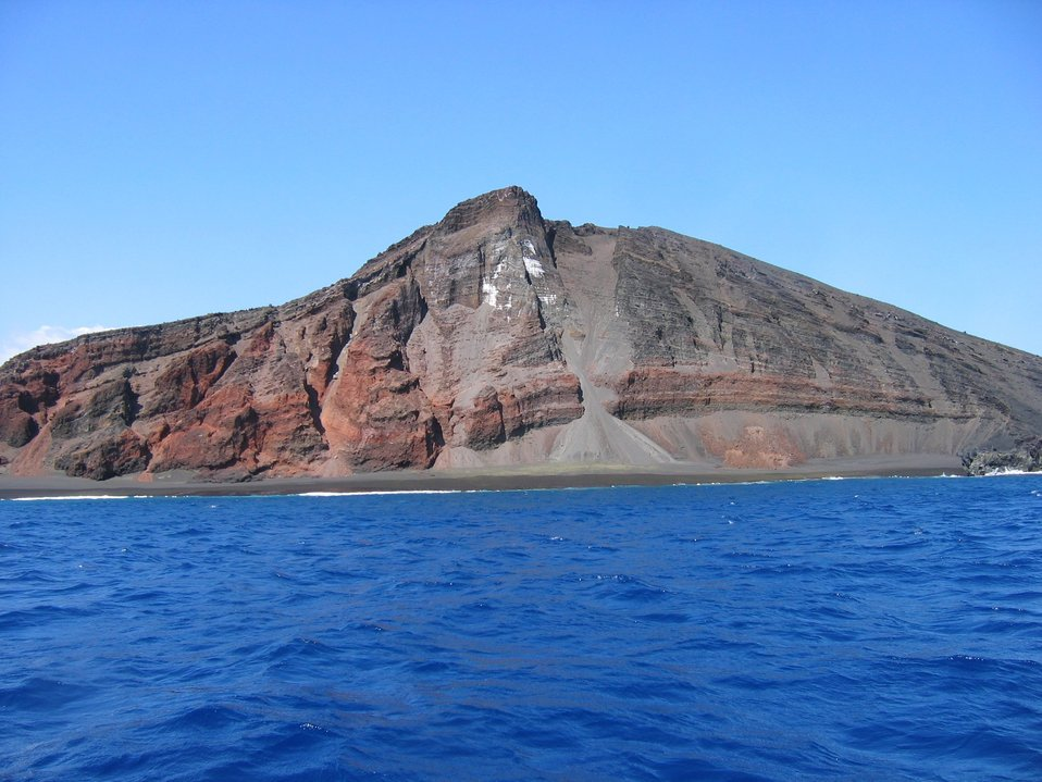 Interior structure of an eroded volcanic cone where it meets the sea.