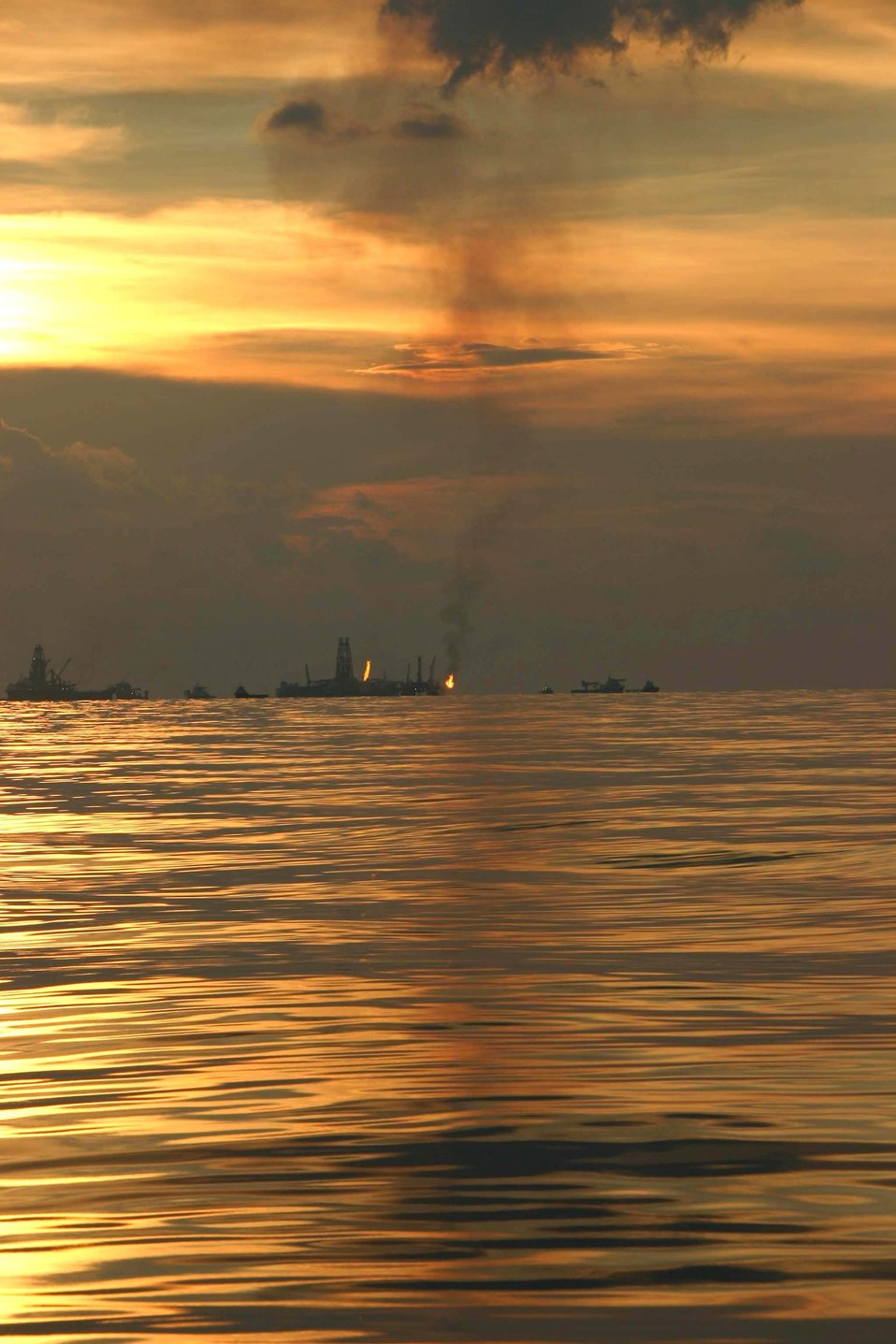 An oil recovery vessel flares gases during the summer 2010 oil spill.  NOAA researchers and colleagues used atmospheric measurements during the spill to derive independent estimates of the recovery rate, oil spill rate and the fate of the spilled gases a