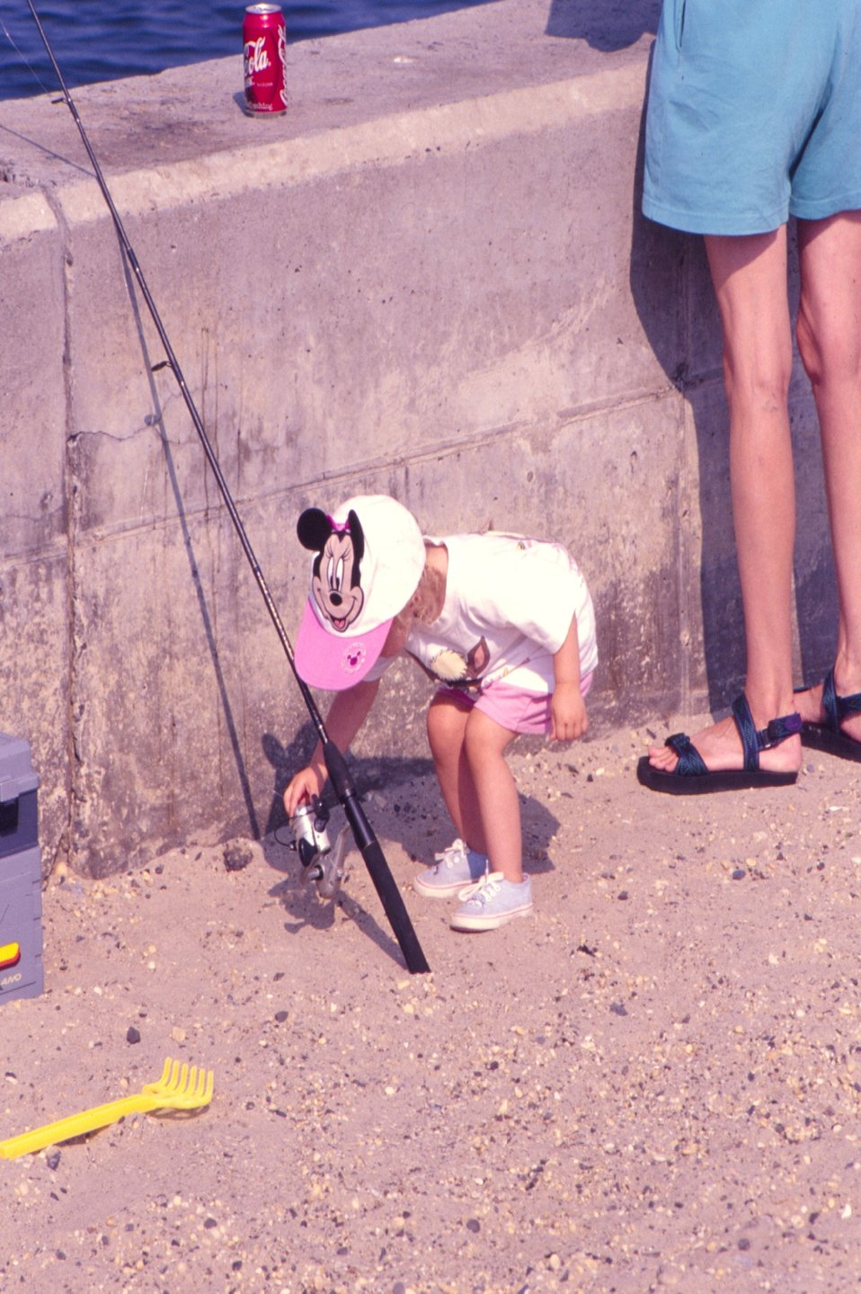 A youthful angling enthusiast checks out the action on her spinning reel. Point Pleasant, NJ.