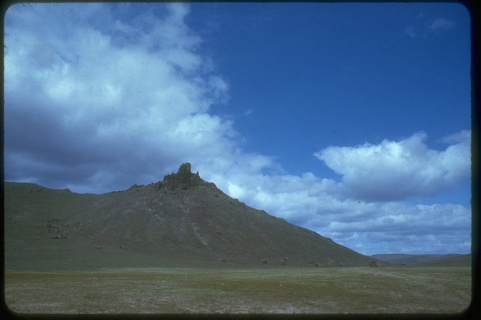 Large rocks and cliffs are set on top of a large hill in the middle of rangeland.  There are also more rocks on the slope of the hill and at the base.