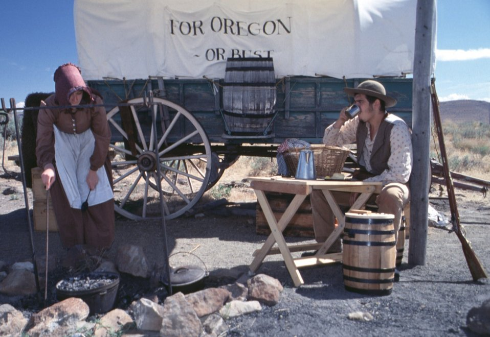 Rebecca Crow and Brandon Kames portray Oregon Trail pioneers at a wagon encampment.