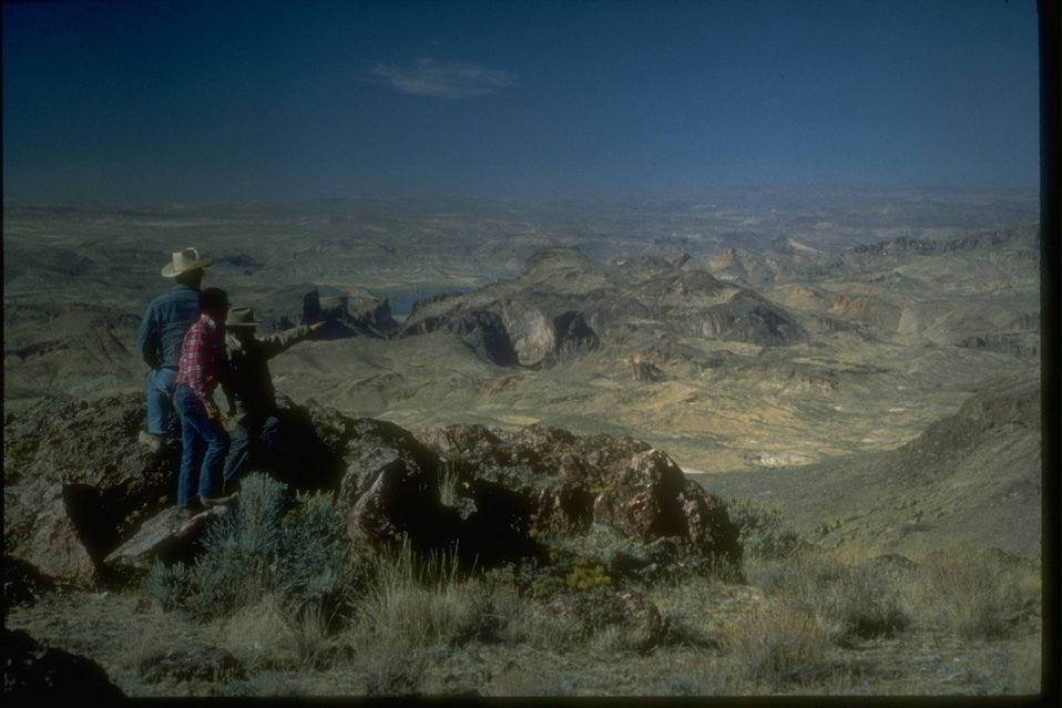 Sightseers lookout over the scenic overlook to a very hilly and rangeland valley floor.