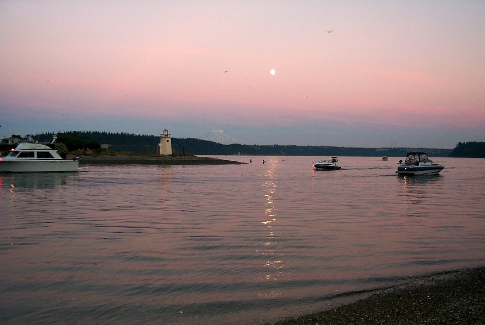 Moonrise over Gig Harbor as salmon fishermen try their luck in the shallows off the spit.  Pleasure boaters are returning to harbor as the day ends. Mt. Rainier is visible in the left center.