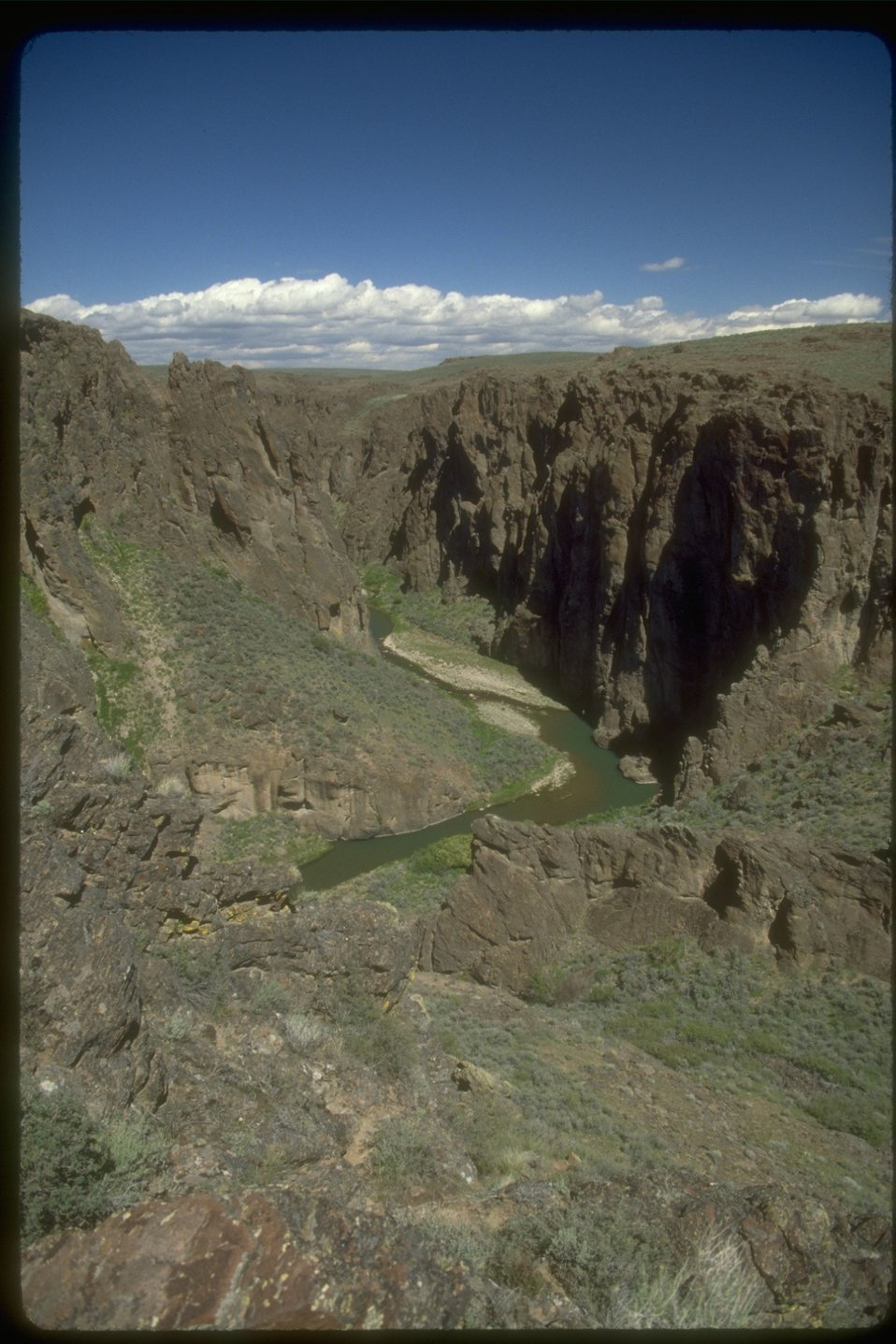 View from canyon rim looking down to the Owyhee River.  There are very steep cliffs going down to the river.