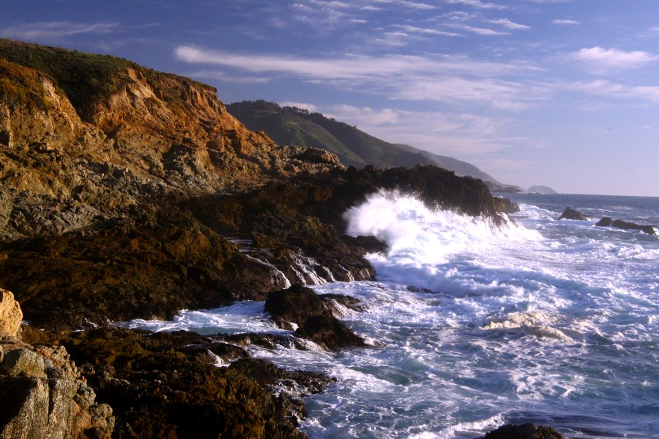 A wave breaking against the rocks of the Granite Canyon area along the Big Sur coastline. Point Sur is seen in the distance.