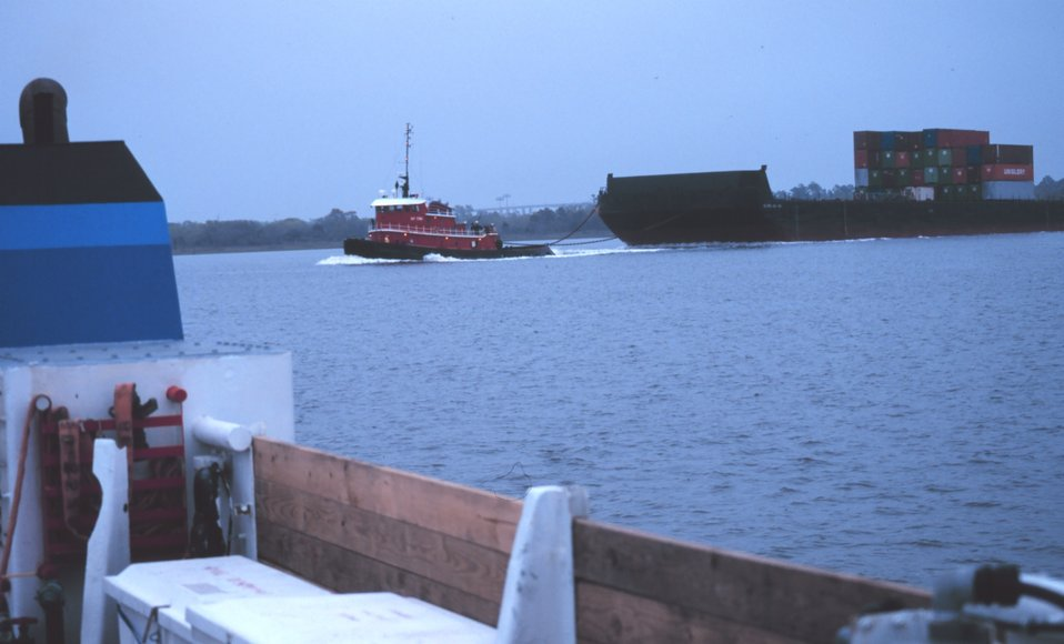 A barge-towing tugboat cruising by the FERREL during status and trends operations in Charleston Harbor.