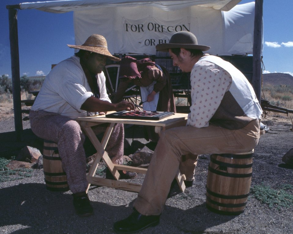 Dylan Prichertt, Rebecca Crow, and Brandon Kames portrqay oregon Trail Pioneers at a wagon encampment.
