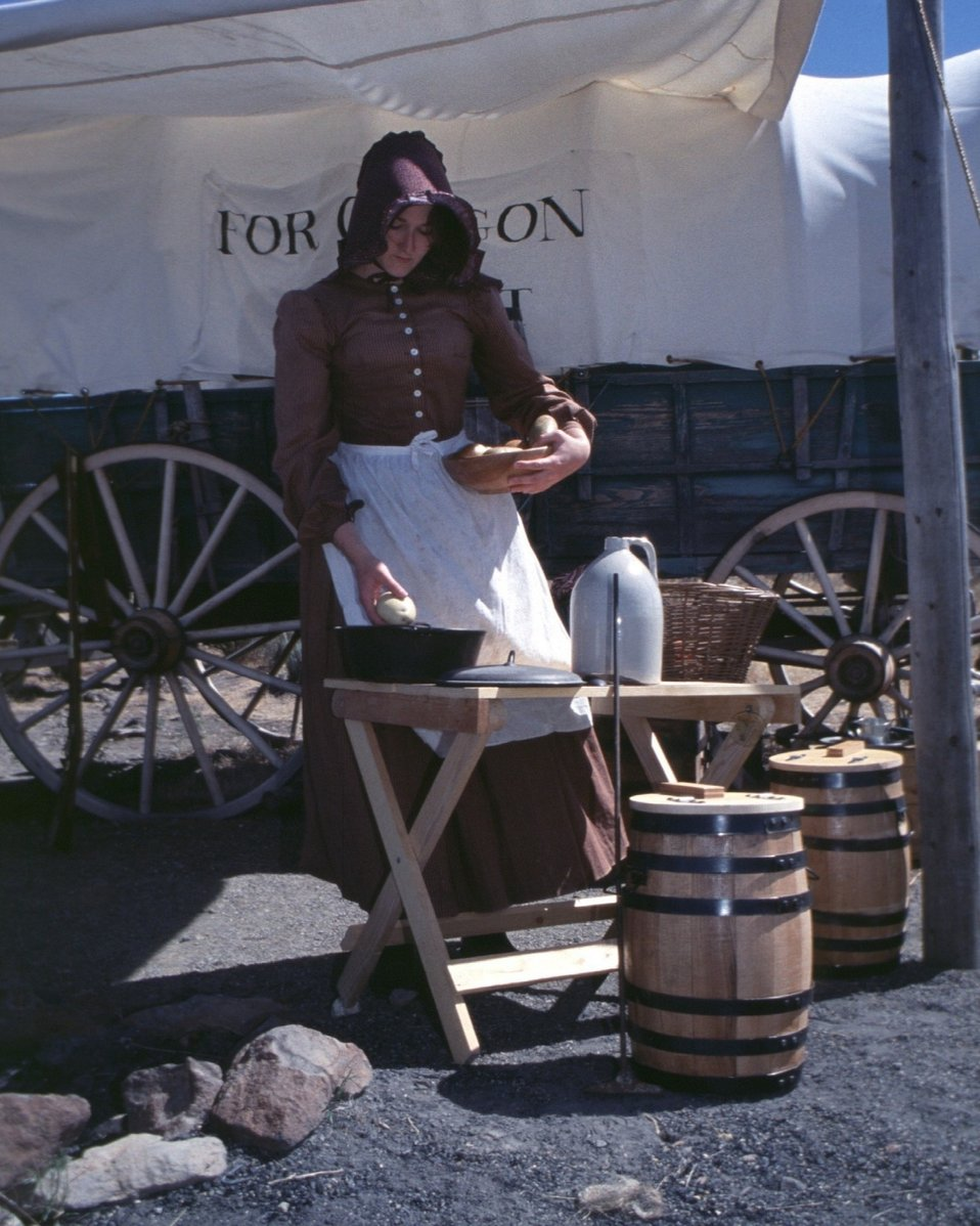Rebecca Crow portrays a pioneer woman cooking on the Oregon Trail.