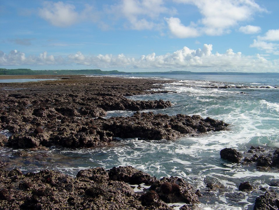 Uncovered reef flat with intervening channels at low tide on the Guam coastline.