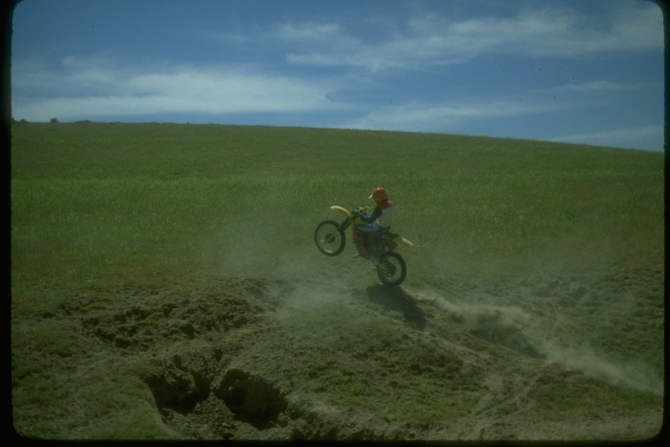 Dirt bike rider jumping his bike over a small hill in the rangeland.