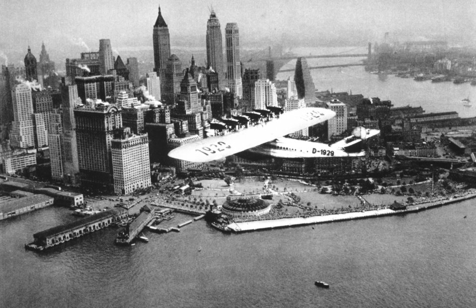 A flying boat cruising by Battery Park at the south end of Manhattan Island.  In: 'Flug Und Wolken', Manfred Curry, Verlag F. Bruckmann, Munchen, 1932.