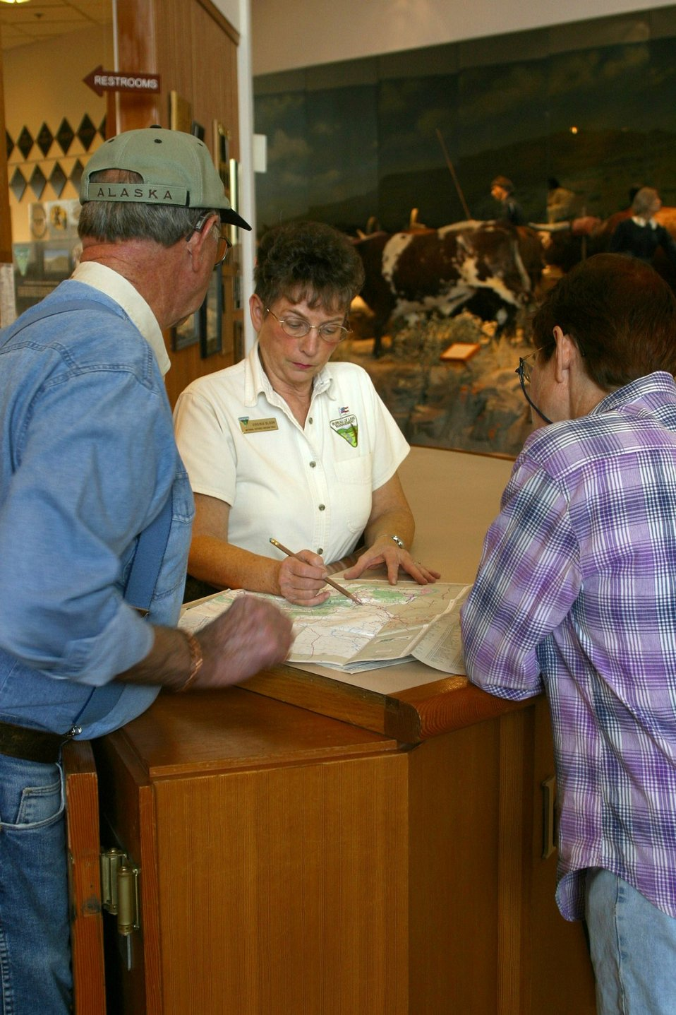 BLM employee Virginia Bloom giving visitors information about the Interpretive Center and the surrounding area.