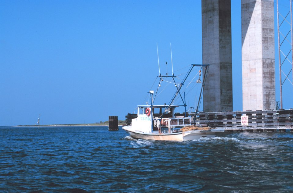 A shrimp boat headed north along the Intracoastal Waterway passing under the JFK  Causeway