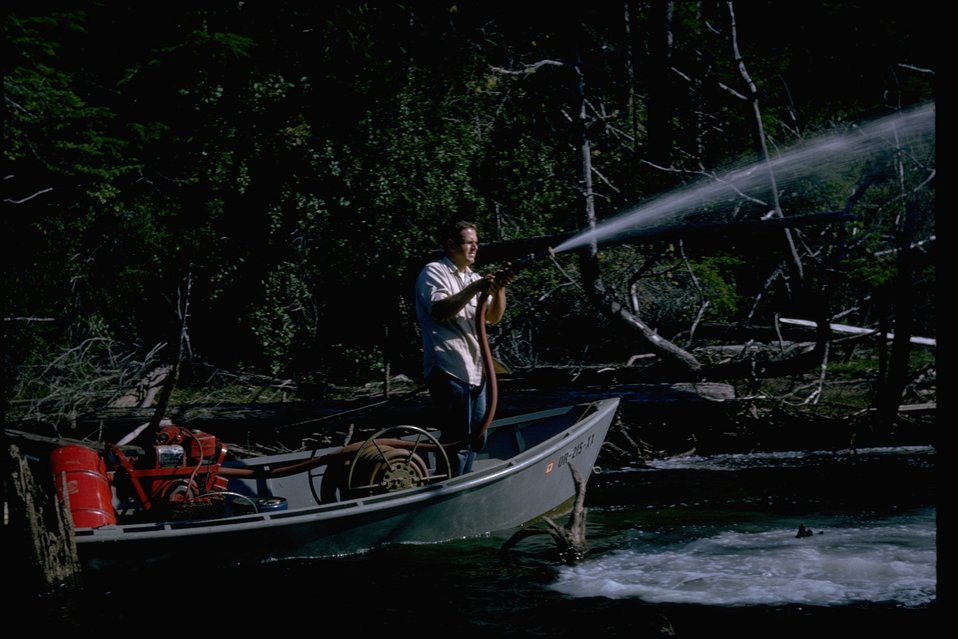 A man standing in a boat with a pump spraying water at something.