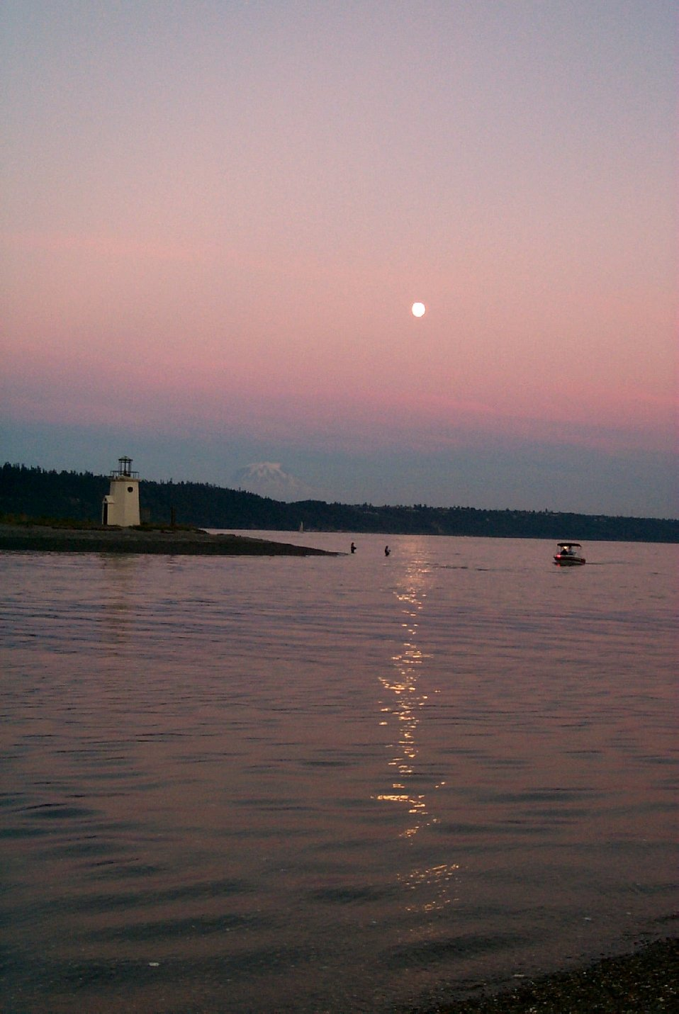 Moonrise over Gig Harbor as salmon fishermen try their luck in the shallows off the spit. Mt. Rainier is visible in the left center.