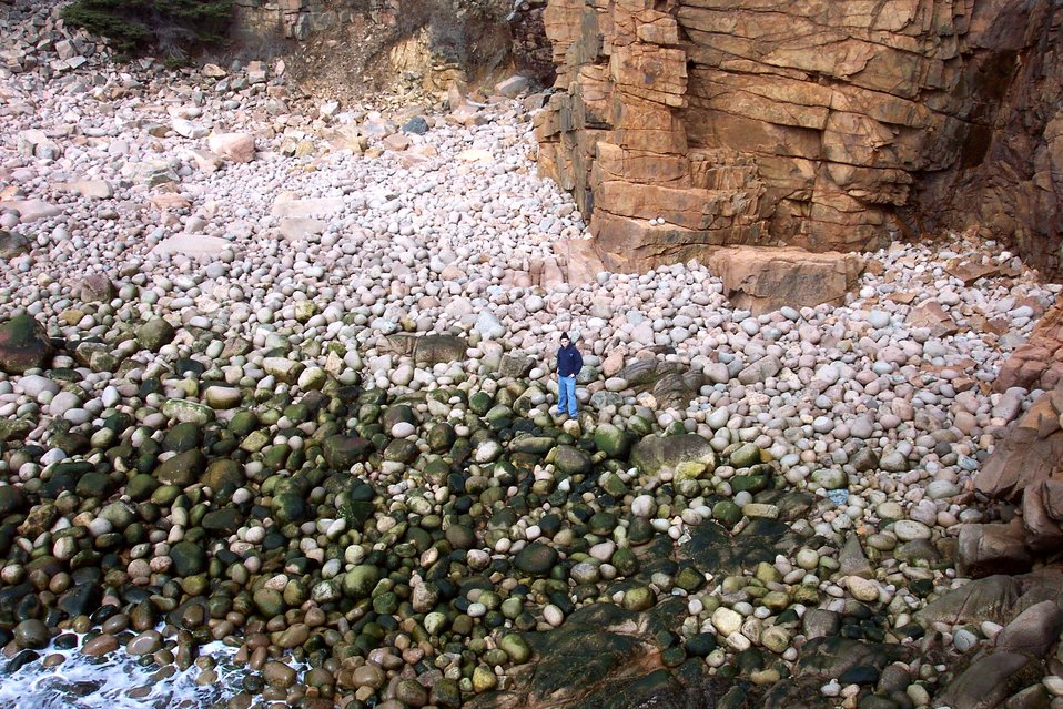 Human being in photo gives scale to 'big' sand.  This is a boulder beach with large stone rollers rounded by the incessant pounding of North Atlantic swells. Some of these boulders are between 1/2 and 1 meter in diameter.  Photo #3 of sequence.