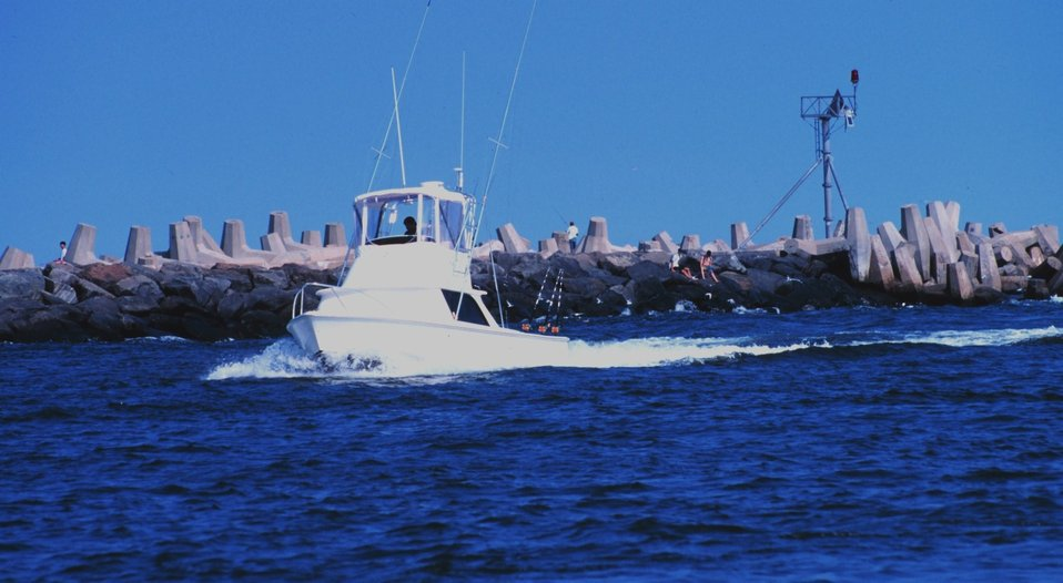 A recreational fishing boat passing the jetties at Manasquan Inlet