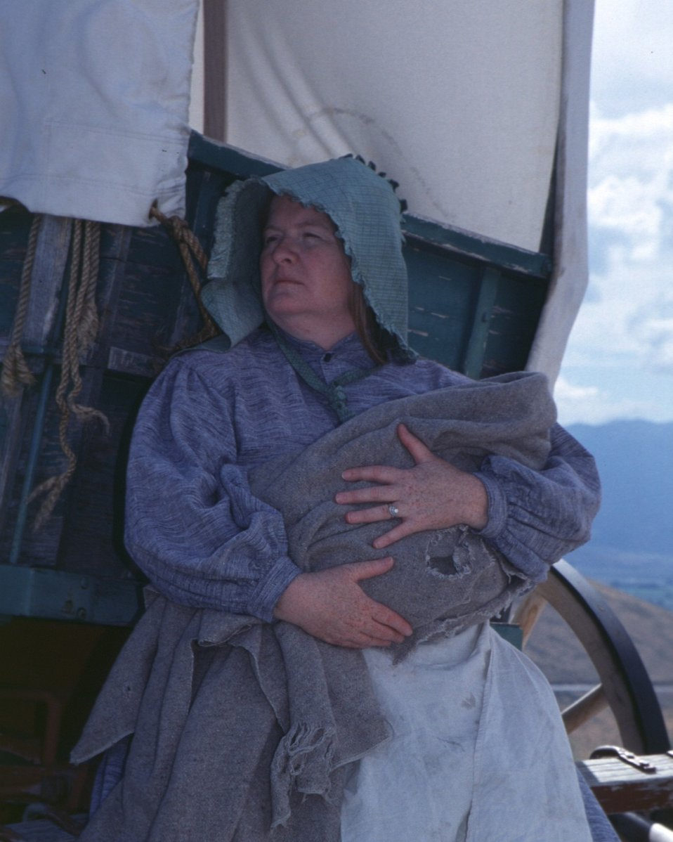Nancy Harms portrays a pioneer woman holding a swaddled child.