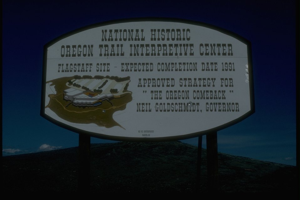 "NHOTIC sign reading: National Historical Oregon Trail Interpretive Center.  Flagstaff Site - Expected Completion Date 1991.  Approved Strategy for ""The Oregon Comeback"".  Neil Goldschmidt, Governor"