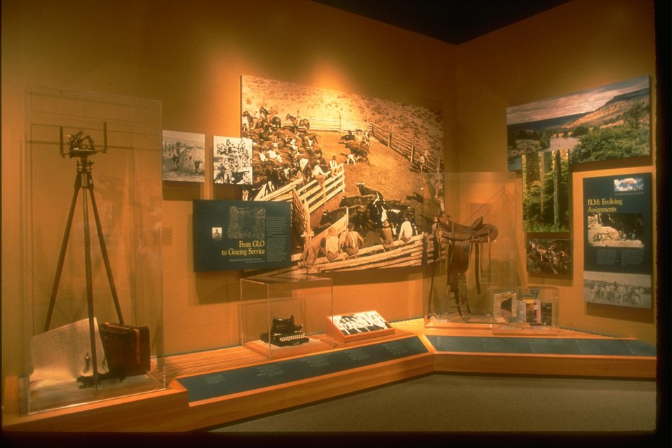 BLM history exhibit with pictures, stories, old camera stand and camera, typewriter, saddle, and books.