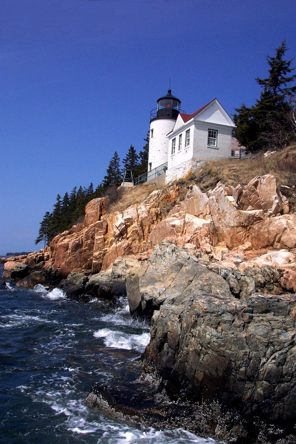 Bass Harbor Head Lighthouse from below and looking east at the shoreline.