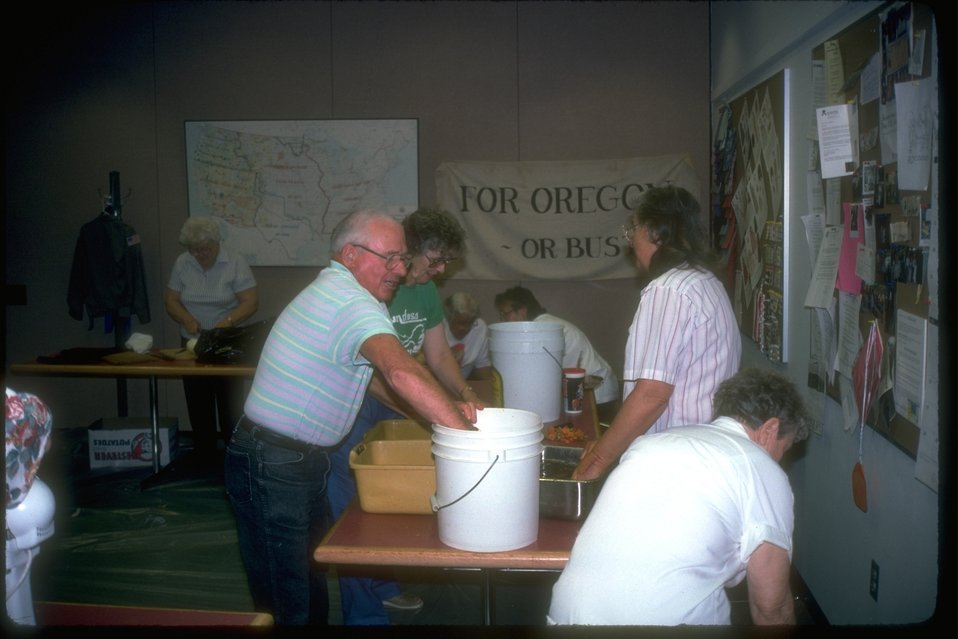 "Volunteers working at a cultural event about Oregon's history.  Sign in background reads, ""For Oregon or Bust."