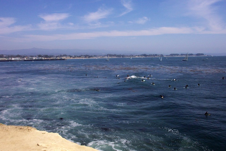 Surfers, sailboats, and the Santa Cruz wharf as seen from Lighthouse Point. Loma Prieta is the high peak in the Santa Cruz Mountains.